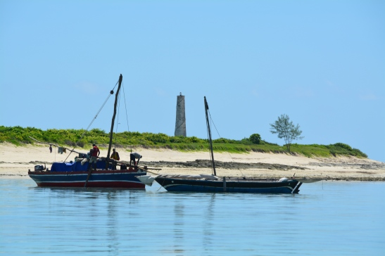 the-old-lighthouse-on-medjumbe-island-visible-from-a-dhow-cruise-amidst-two-other-traditional-dhows
