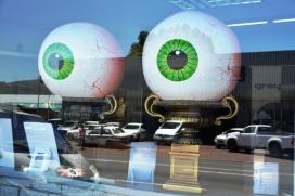 Voortrekker Road reflects in an optometrist's window