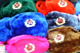 Garish furry hats for sale at a pavement stall