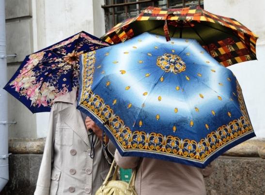 In Nevsky Prospekt babushkas huddle under umbrellas for a quick session of gossip