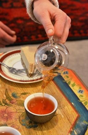Tee met ongebakte pynappelkaaskoek by 'n geblomde houttafel