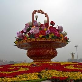 Die stadslug van Beijing is dynserig, maar die blomme staan vol in die bloei