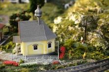 Die modeltrein in Model Railroad Specialists tjoekepakke verby 'n spitsdakgeboutjie en 'n man wat onder 'n boom staan en piepie