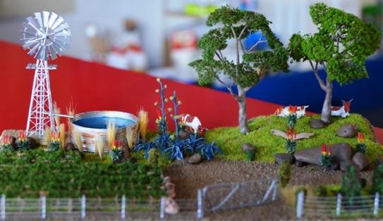 'n Suid-Afrikaanse plaastoneel met aalwyne, koeie, 'n windpomp en 'n plaasdam op 'n treinmodelaanleg