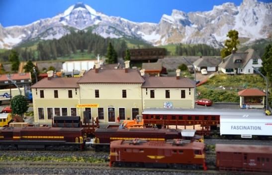 Op die treinmodelaanleg binne die winkel ry drie treine op drie spoorlyne voor sneeubedekte berge verby voor hulle by die Matchbox-stasie stop