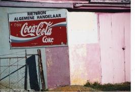Die pienk muur, dak en deur van Rietbron Algemene Handelaar is deur die Karoo-son bygekom