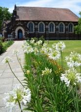 'n Tuinpaadjie omsoom met wit agapantusse lei van die Klein Kerk na die Groot Kerk op die perseel van die St George Anglikaanse Kerk
