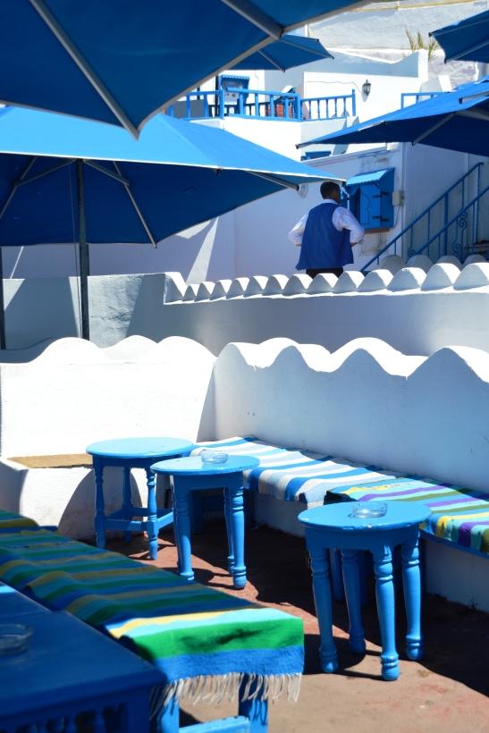 Cafe des Delices se tafeltjies, stoeltjies en kussings het dieselfde kleurskema as die huisies met hul blou deure en vensters in Sidi Boe Said