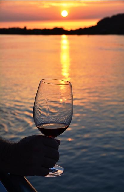 'n Glas wyn terwyl die son oor die rivier sak